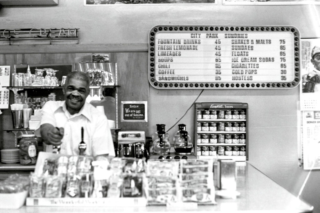 Interior view of City Park Sundries at 2101 York Street in the City Park West neighborhood. Mr. Ferris Cassius, the proprietor, draws a beverage from the soda fountain behind the counter. 1976.