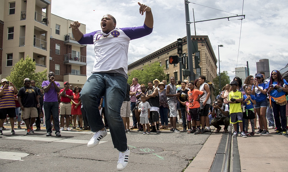 Danny Perkins gets airborn as the Omega Psi Phi Fraternity crosses Welton Street. The Juneteenth parade in Five Points, June 17, 2017. (Kevin J. Beaty/Denverite)