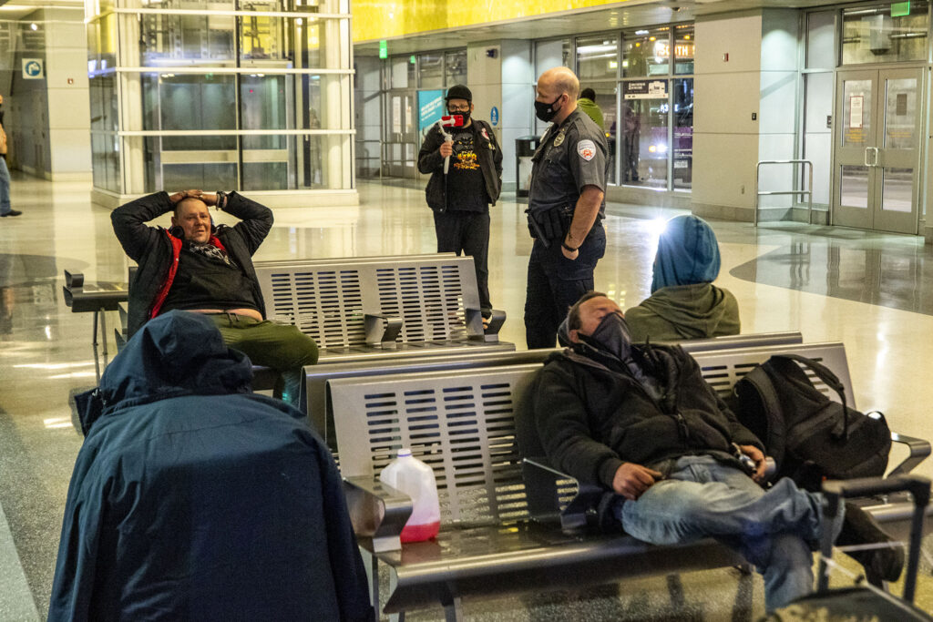 A security officer tells a man sleeping in Union Station's bus terminal to wake up and leave. Feb. 3, 2021.