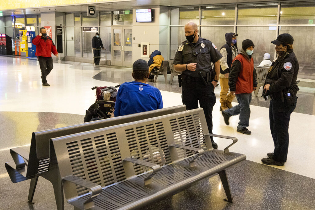 A security officer tells a Timothy Renault, who was sleeping in Union Station's bus terminal, to wake up and leave. Feb. 3, 2021.