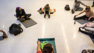 A small group of protesters do yoga during a sit-in against new rules barring sleeping and sitting on the ground inside Union Station's bus terminal. Feb. 3, 2021.