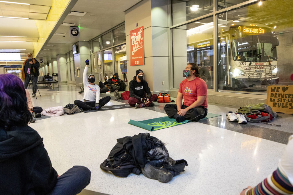 A small group of protesters hold a sit-in against new rules barring sleeping and sitting on the ground inside Union Station's bus terminal. Feb. 3, 2021.