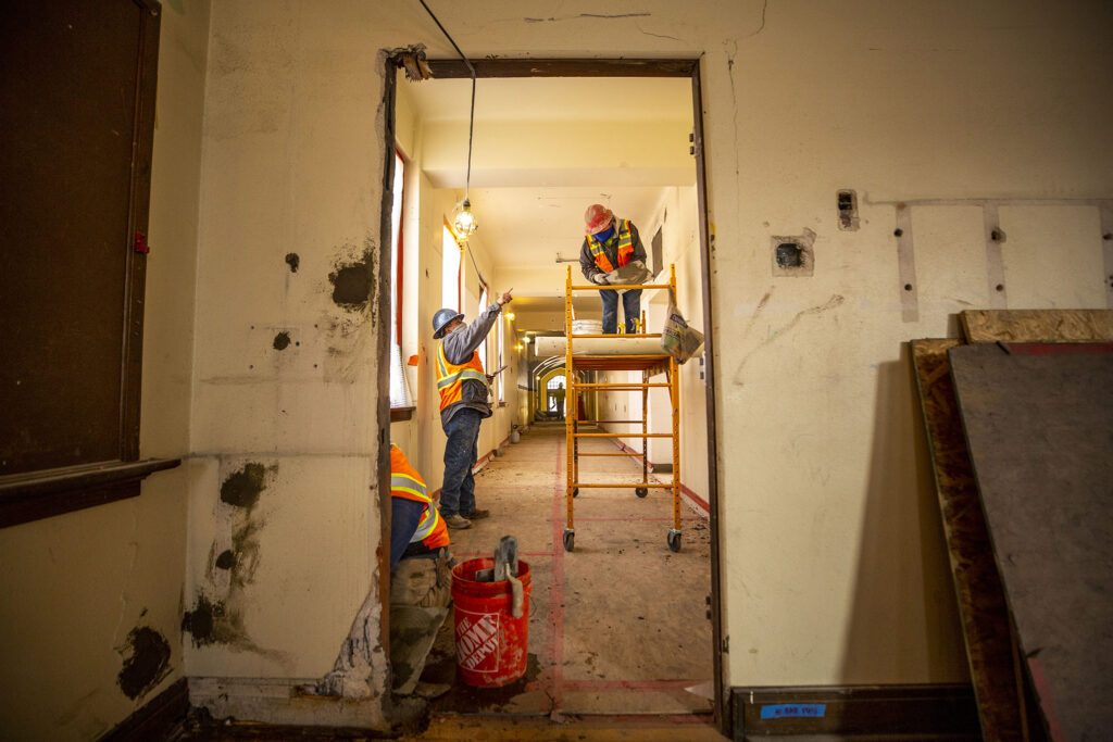 Workers transform the historic Pancratia Hall at Loretto Heights into affordable housing units. Harvey Park South, Feb. 10, 2021.