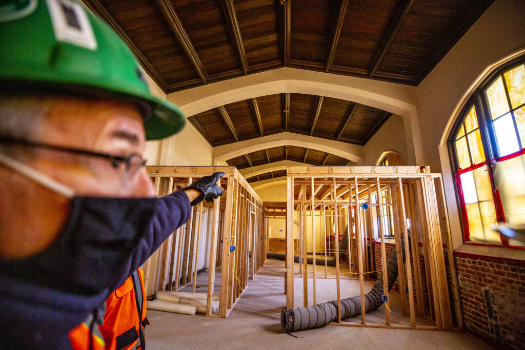Jim Hartman pers into an old chapel inside Loretto Heights' historic Pancratia Hall, which will soon be an affordable housing unit with very tall ceilings. Harvey Park South, Feb. 10, 2021.