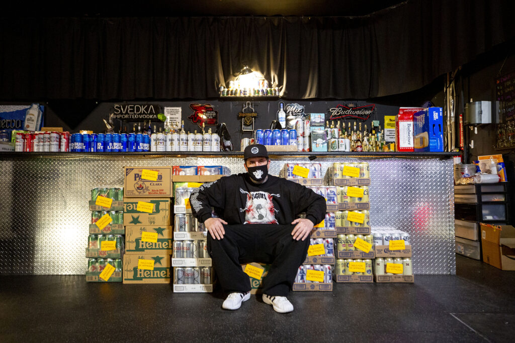 Ivan Ovchinnikov sits on cases of beer, that expired while he was shuttered for the pandemic, inside his Roxy Theatre on the 2500 block of Welton Street in Five Points. Feb. 19, 2021.