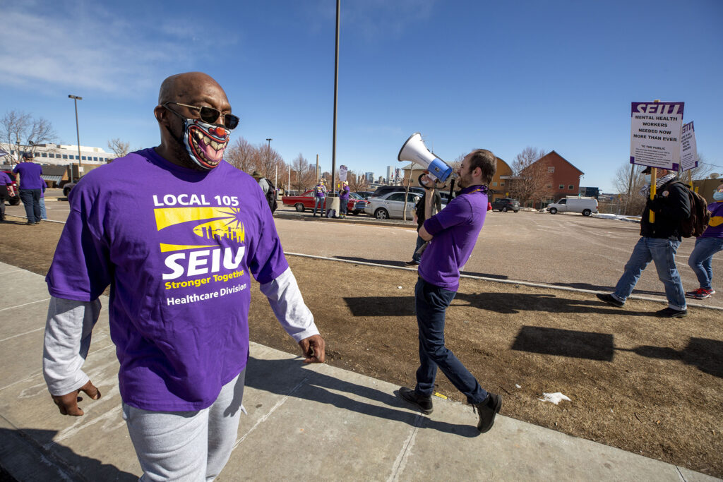 Benjamin Franklin, a counselor with the Mental Health Center of Denver, pickets with colleagues and supporters along Federal Boulevard for higher and more predictable wages. Feb. 20, 2021.