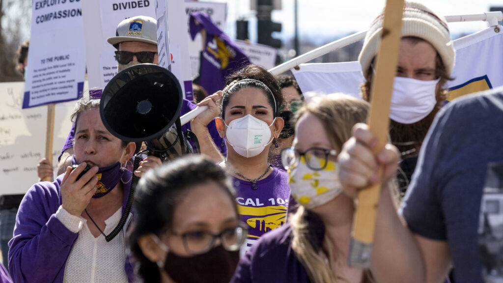 Candice Vigil, who helps Mental Health Center of Denver clients get work in foodservice, pickets with colleagues and supporters along Federal Boulevard for higher and more predictable wages. Feb. 20, 2021.