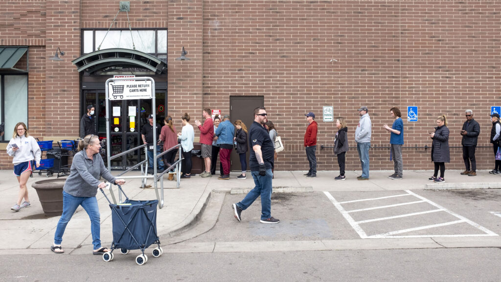 "A line at Argonaut Wine and Liquors in Capitol Hill appeared soon after Mayor Michael Hancock announced a ""shelter in place"" order and quickly stretched around the building. March 23, 2020. (Kevin J. Beaty/Denverite)"