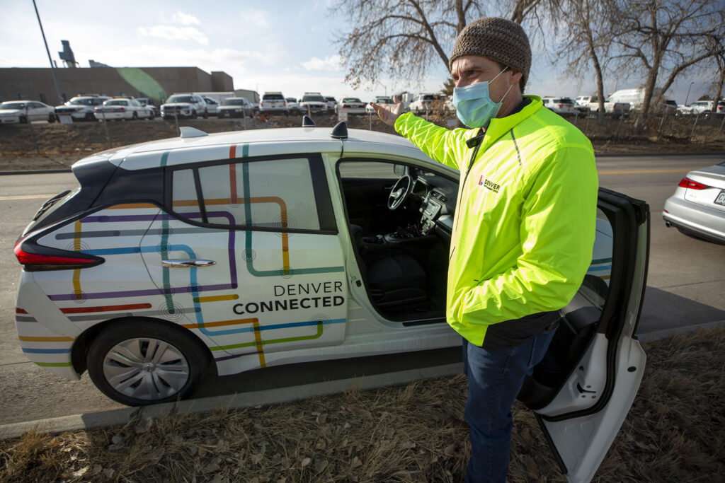 """Michael Finochio, transportation engineer with the Denver Department of Transportation and Infrastructure, shows off one of Denver's """"connected vehicles"""" that can talk to stoplights. Feb. 11, 2021. Feb. 11, 2021."""
