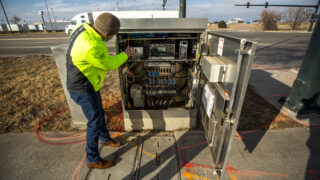 Michael Finochio, transportation engineer with the Denver Department of Transportation and Infrastructure, shows off the guts of a stoplight array that contains technology to talk to connected vehicles. Feb. 11, 2021.