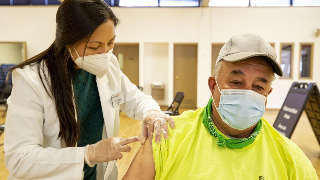 Nhung Mai gives  Demetrio Rodriguez a COVID-19 vaccine at a city-run clinic inside the Barnum Recreation Center. March 10, 2021.