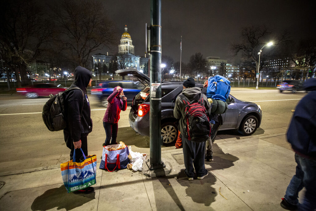 Harmony Cummings distributes blankets and clothes to people living on Denver's streets before heavy snow was expected in the city. March 12, 2021.