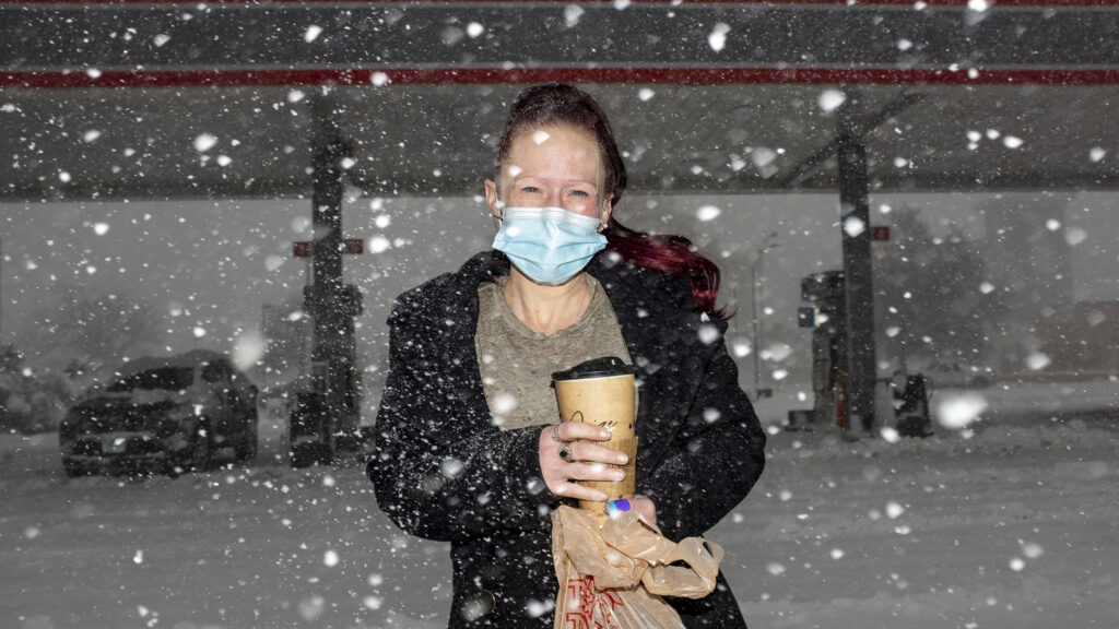 Christy Johnson stands in the snow outside of a Montbello gas station. March 14, 2021.