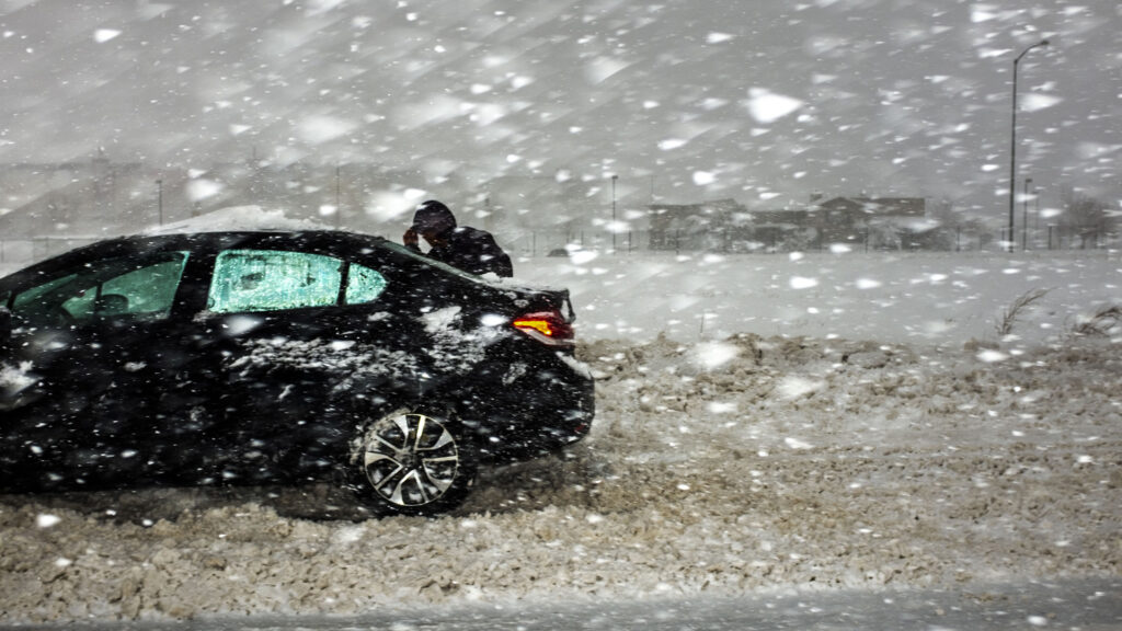 A man assesses his car, which is stuck on the side of I-70, on March 14, 2021.
