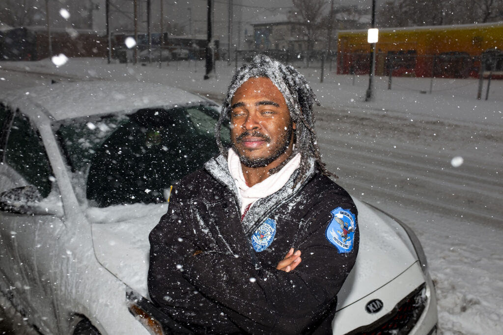 Marvin Johnson stands with his car, which is stuck in the snow on Park Avenue and will remain stuck there for a little while longer. March 14, 2021.