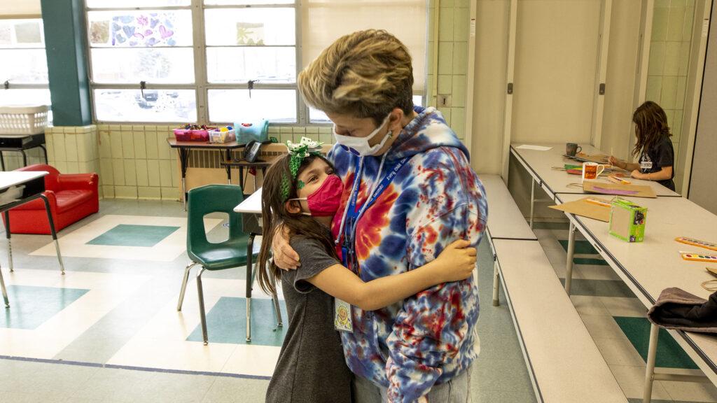 Rylan, a second-grader, hugs Carson Elementary Discovery Link leader Jennifer Piel before regular classes begin on March 17, 2021.