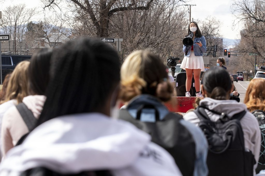 Ally Yager, an East High School junior and president of the school's Asian Pacific Islander Student Alliance, speaks to students gathered during a walk-out in solidarity with Boulder on Thursday afternoon. March 25, 2021.