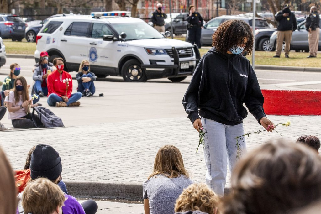 Kaliya Carrillo, who helped organize a walk-out at East High School in solidarity with Boulder, passes out flowers to students huddled in front of the building. March 25, 2021.