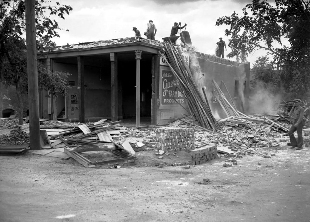 Men work to demolish a building as part of the Denver Housing Authority Lincoln Park project located  between 13th Avenue and Colfax, and Mariposa and Osage Streets, circa 1940.