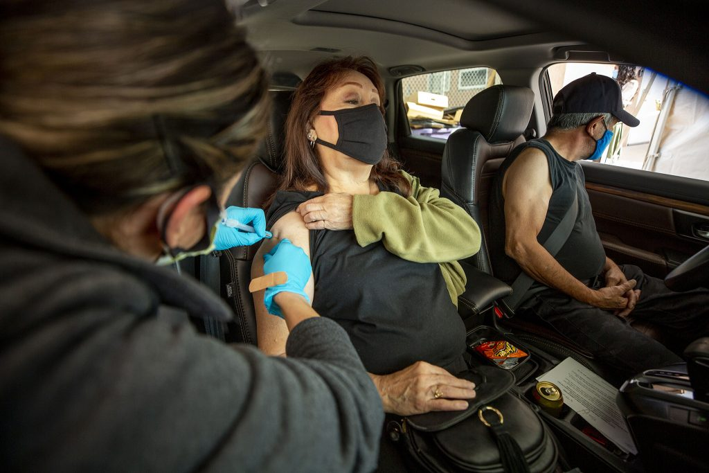 Cora Ornelas gets a COVID-19 vaccination in a drive-through clinic behind Globeville's Clinica Tepeyac. March 26, 2021.