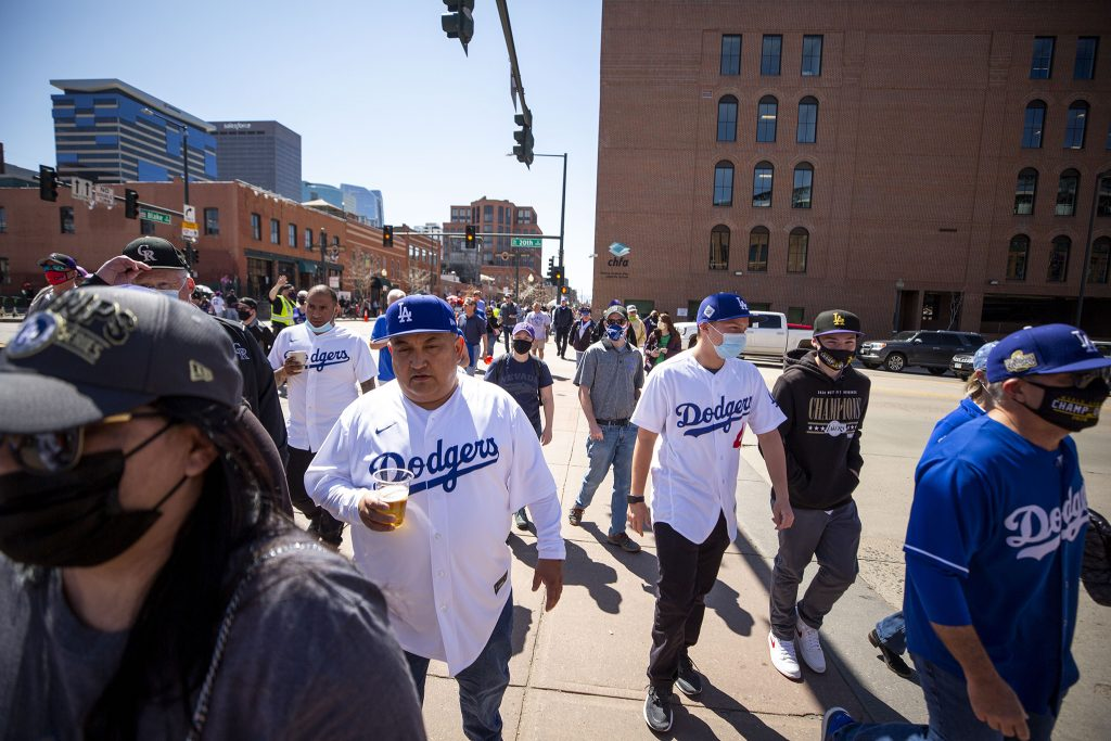 Fans pour across 20th Street towards Coors Field before the Rockies face off against the Los Angeles Dodgers on opening day. April 1, 2021.