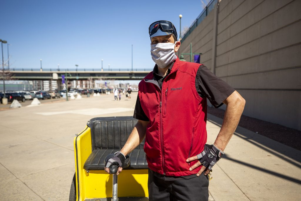 Mark Chavez stops for a moment after dropping a pedicab customer off at the entrance of Coors Field on Opening Day. April 1, 2021.
