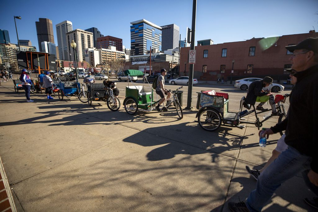 Pedicab drivers wait in line to pick up people leaving Opening Day at Coors Field. April 1, 2021.