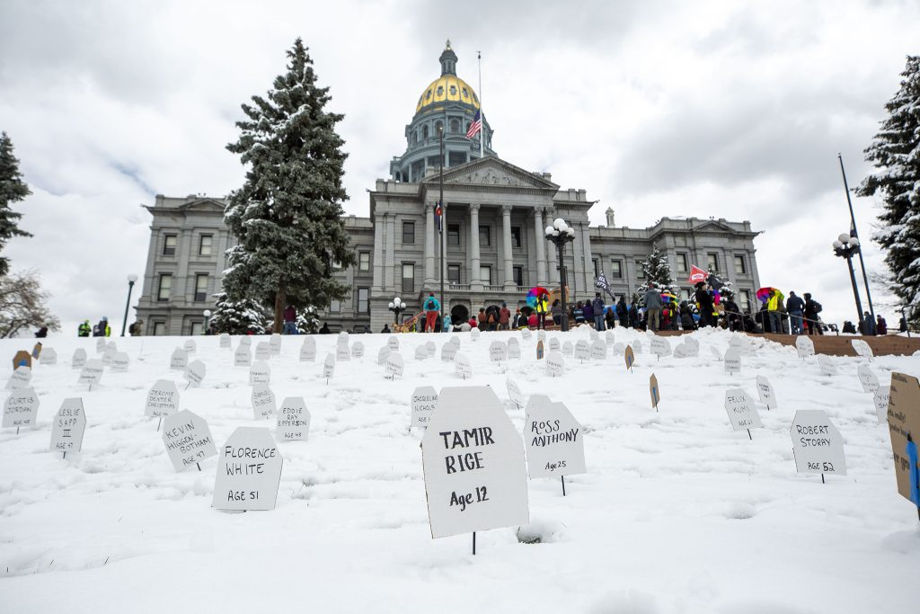 Makeshift gravestones cover the snowy lawn in front of the State Capitol during a protest against police brutality. April 17, 2021.