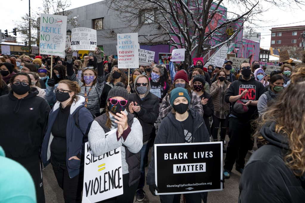 A march against police brutality stops in front of Denver Police District 6 headquarters on April 17, 2021.