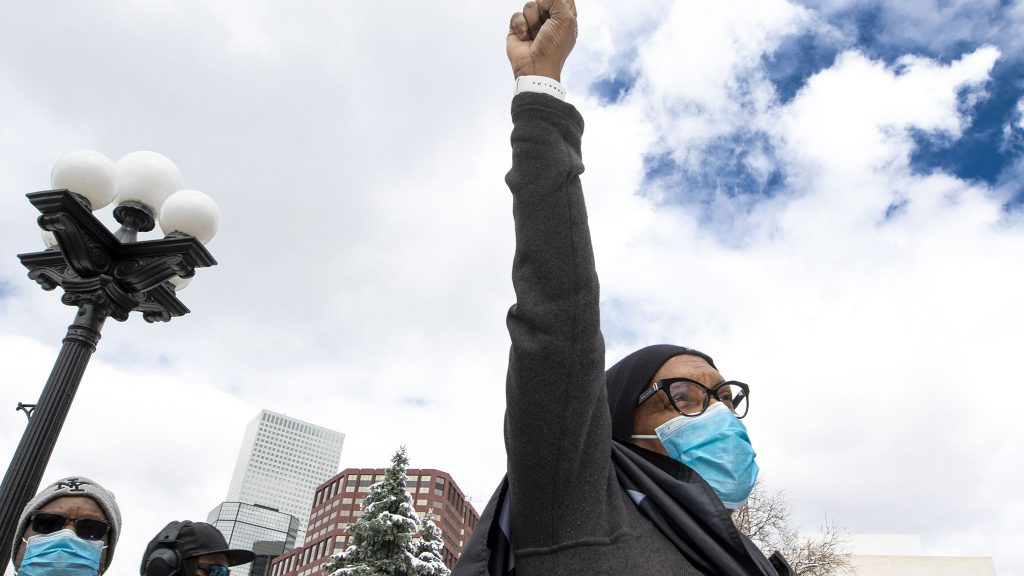 Alice Hayes raises a fist during the first of two protests at the Capitol against police brutality. April 17, 2021.
