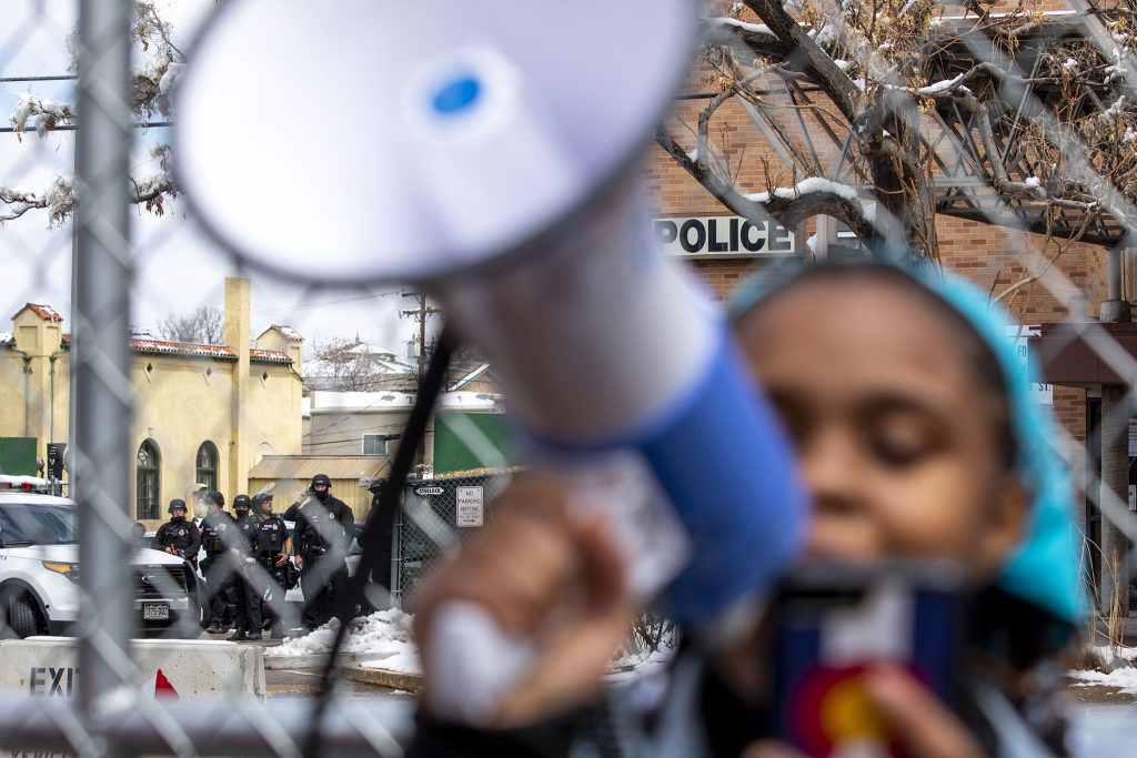 Denver Police officers wait at the ready outside of the department's District Six headquarters as Ashira Campbell reads the names of people killed by police across the nation. April 17, 2021.