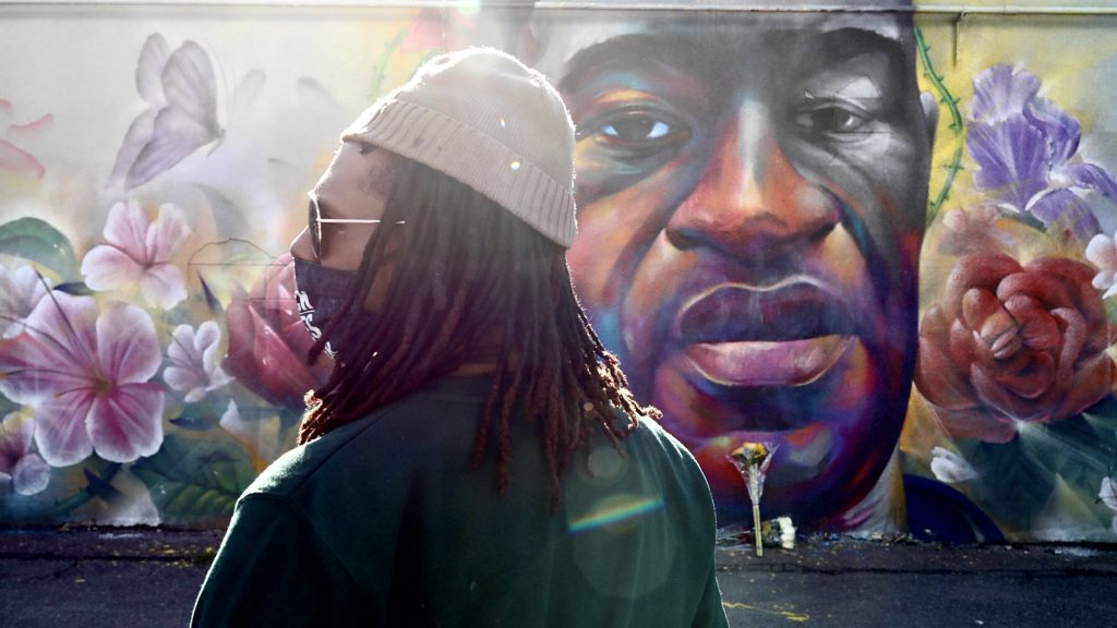 Quincy Shannon, who led some of last summer's Denver protests in the aftermath of George Floyd's killing, pays his respects at the mural of Floyd by artist Detour on Tuesday.