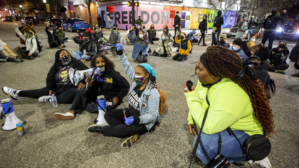 Protesters led by Aariyah Johnson (left to right), Rahma Ahmed, Ashira Campbell and Iris Butler hold the intersection of Colfax Avenue and Washington Street for ten minutes. April 23, 2021.
