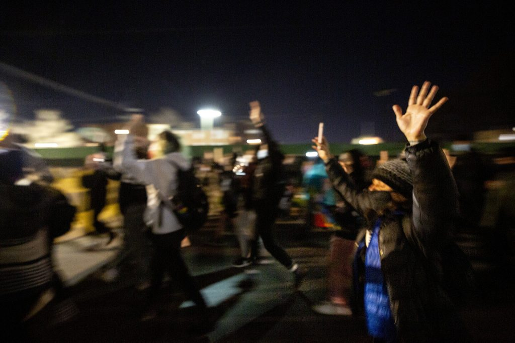 Marchers pass Denver Police's District 6 headquarters with their hands up. April 24, 2021.