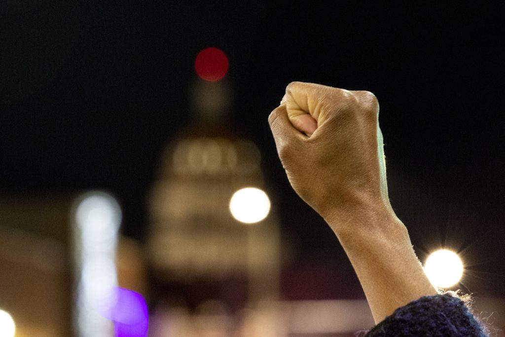 Porshai Campbell holds up a fist as protesters decrying the killing of Ma'Khia Bryant hold the intersection of Colfax Avenue and Washington Street for ten minutes. April 23, 2021.