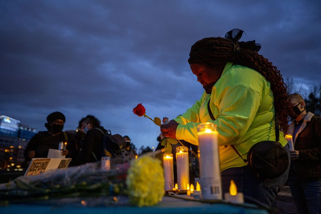 Iris Butler lights candles before a vigil mourning people killed by police in America at Commons Park. April 23, 2021.