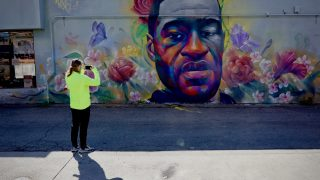 Jared O of Denver stops to take a photo of the George Floyd mural on Colfax at High Street in Denver Tuesday.