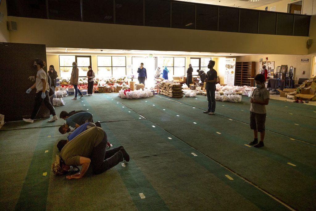 Scout Troop 218 members pray as volunteers pack bags for a Ramadan food ride at the Colorado Muslim Society on Parker Road.  April 10, 2021.