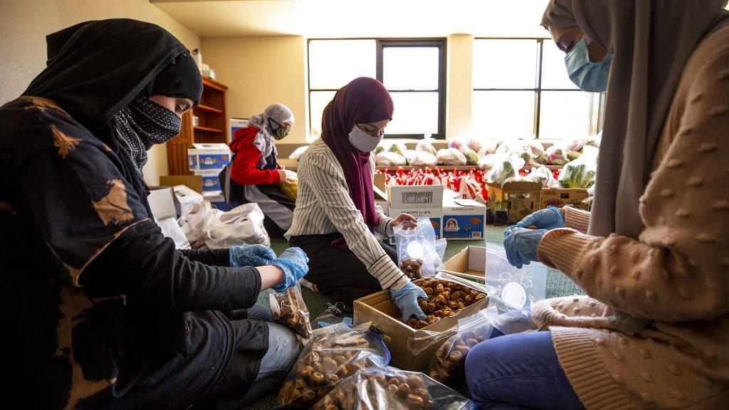 Safa Hama, Sarah Alruwayi and Etaf Alghunaim fill bags with dates during a Ramadan food drive at the Colorado Muslim Society on Parker Road. April 10, 2021.