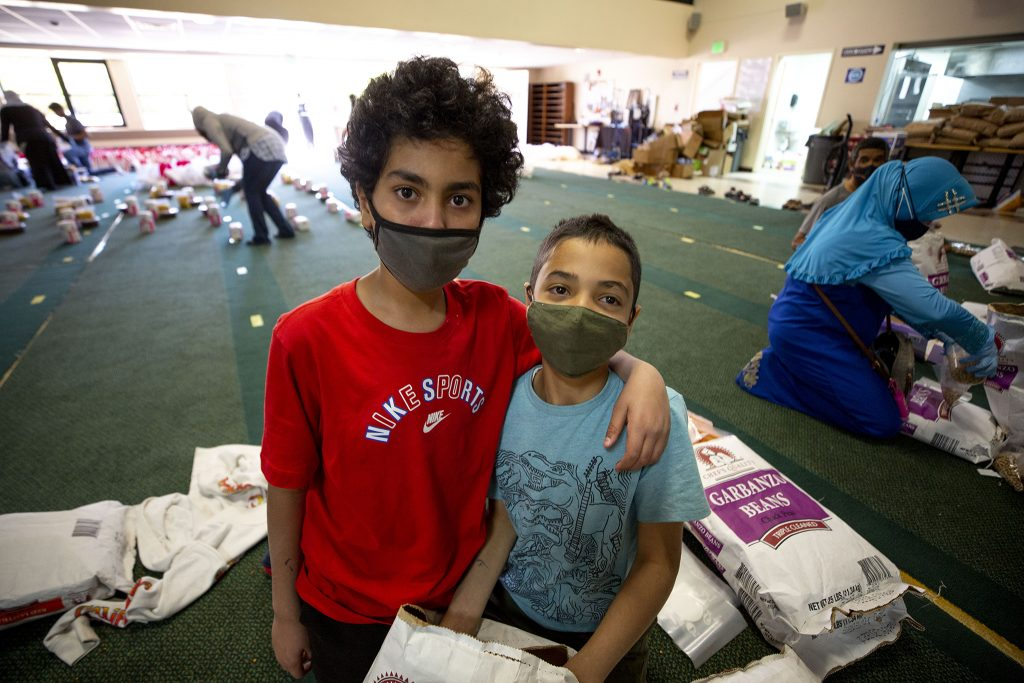 """""""Best friends"""" Abdul and Abdul work with their Cub Scout troop to fill bags for a Ramadan food drive at the Colorado Muslim Society on Parker Road. April 10, 2021."""