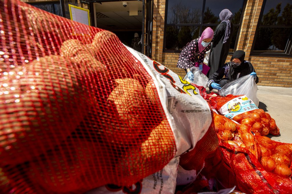 Mariam Harasis and Habiba Samir unload onions during a Ramadan food ride at the Colorado Muslim Society on Parker Road.  April 10, 2021.