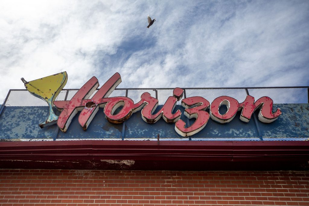 A bird flies out of a hole in the Horizon bar sign near the corner of 33rd Avenue and Holly Street in Northeast Park Hill.  May 8, 2021.