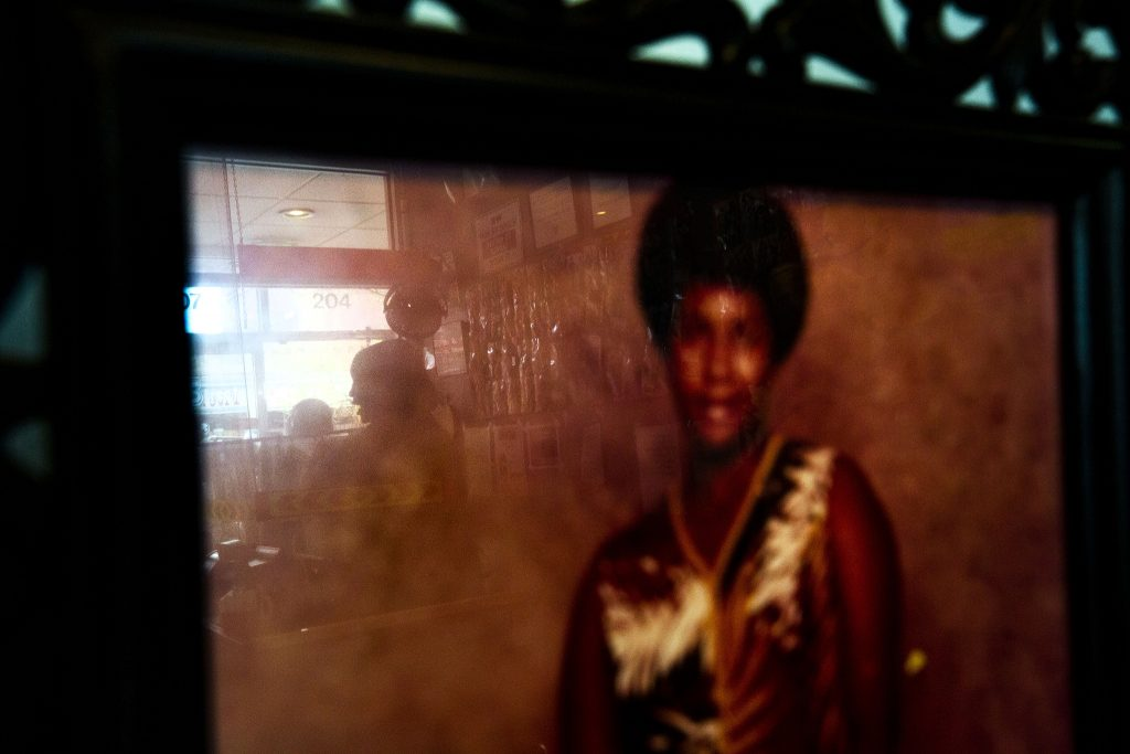 Fathima Dickerson can be seen reflected in a portrait of her mother, Mona, who founded the Welton Street Cafe. May 8, 2021.