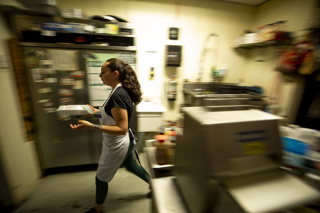 Katie Monroe rushes a to-go order out from the kitchen. Welton Street Cafe. May 8, 2021.
