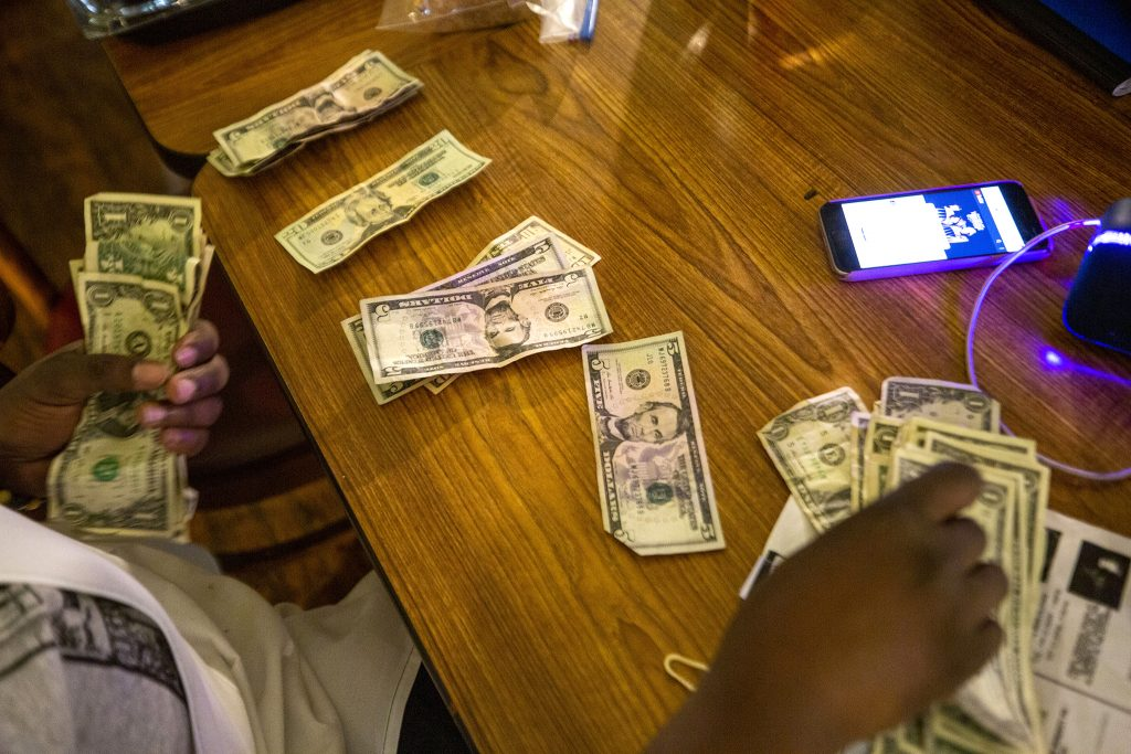 Fathima Dickerson counts money from the Welton Street Cafe's register after a busy night. May 8, 2021.