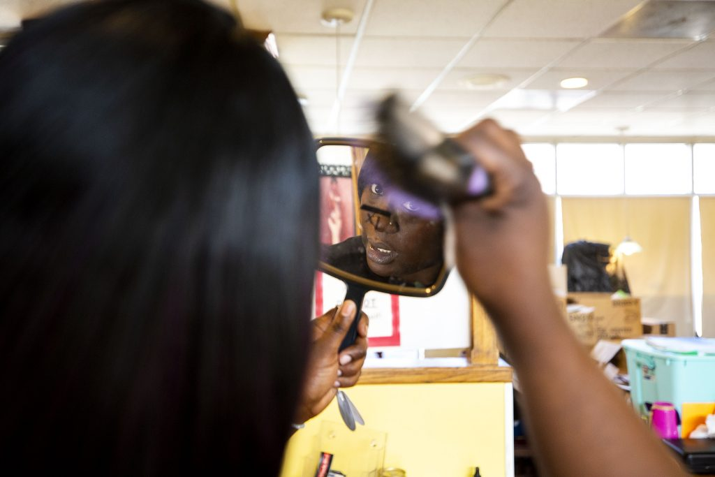Fathima Dickerson fixes her hair before Welton Street Cafe opens for the day. May 8, 2021.