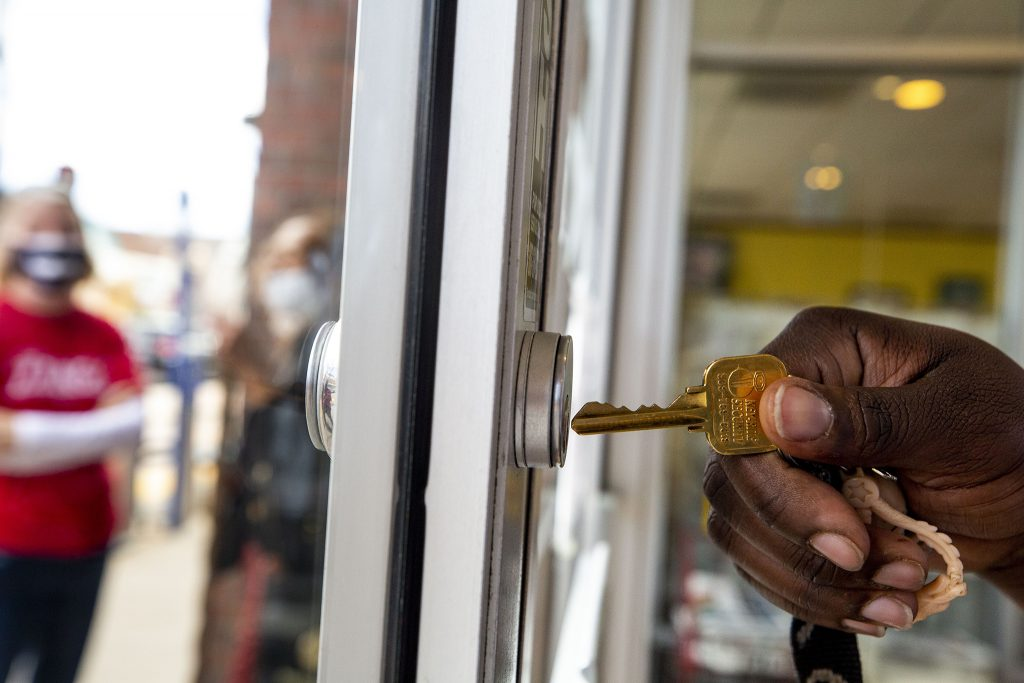 A small crowd waits outside of the Welton Street Cafe as Fathima Dickerson unlocks the front doors to open for the day. May 8, 2021.