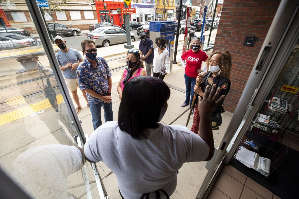 Fathima Dickerson tells the crowd waiting outside Welton Street Cafe how their COVID-era ordering process works. May 8, 2021.