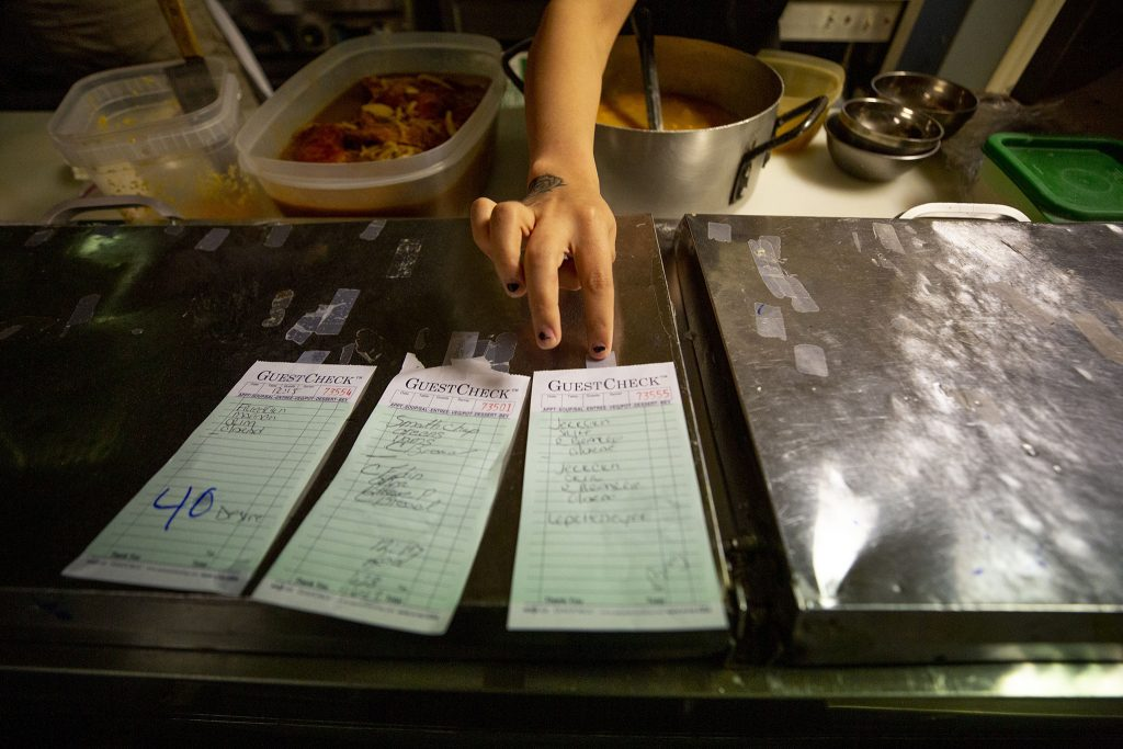 Katie Monroe sticks order tickets to a chrome cabinet in the Welton Street Cafe kitchen as orders begin to flood in. May 8, 2021.