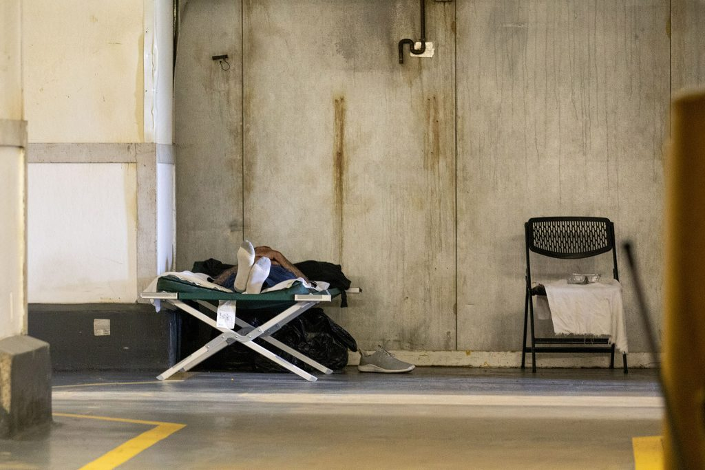 A man rests on a cot inside the Salvation Army's Crossroads shelter off Brighton Boulevard in Five Points. May 20, 2021.